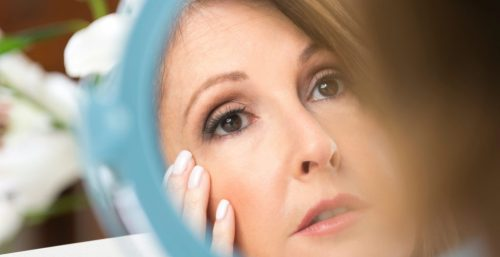 A woman checking the mirror for skin tags at cosmetic laser dermatology in san diego, ca