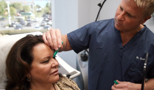 Dermatologist doing face mapping on the face of a female patient for Botox injections, San Diego, CA